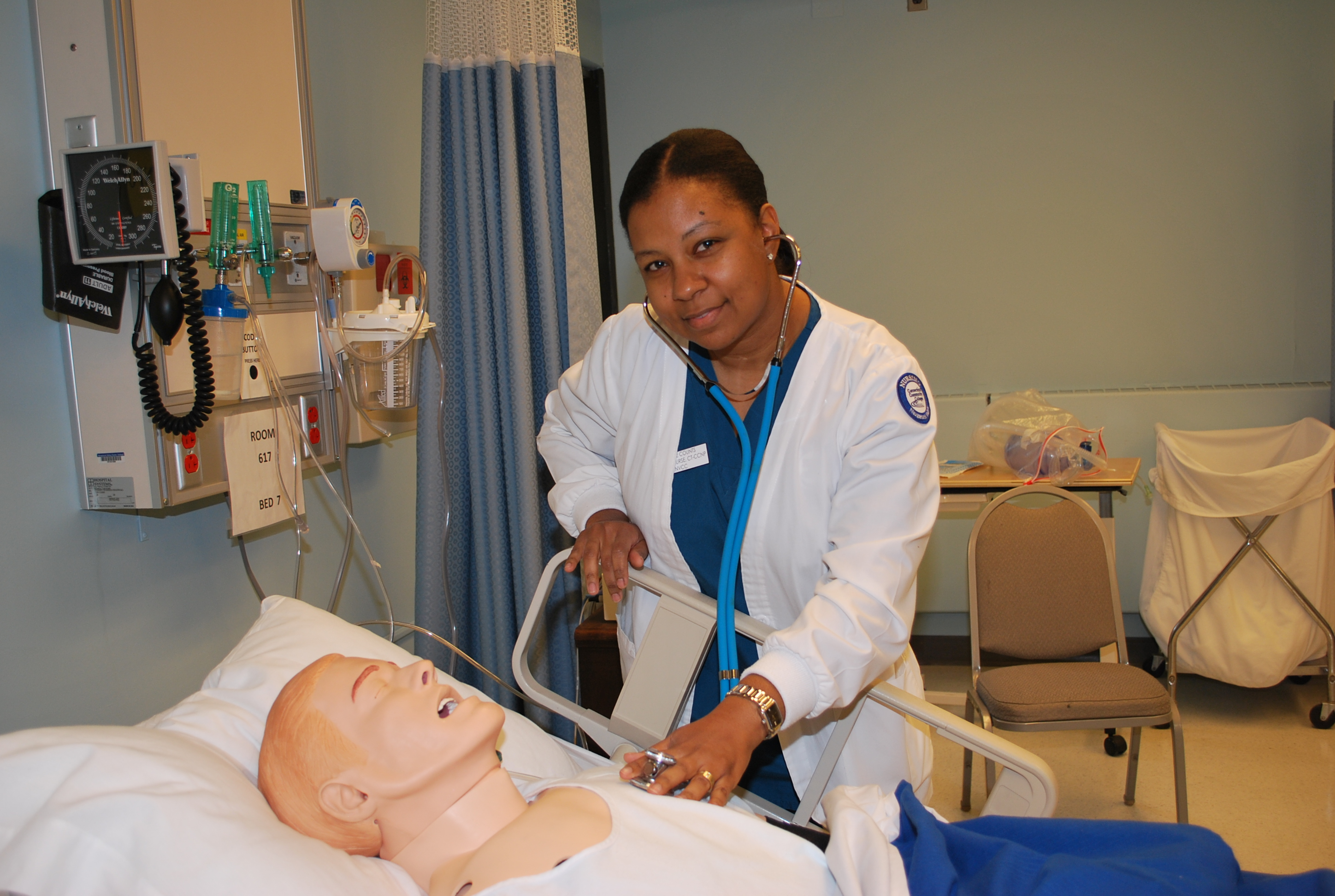 NVCC Nursing student simulating care using a stethoscope on a mannequin laying in a hospital bed.